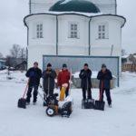 Прихожане убирают территорию монастыря от снега.